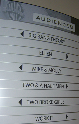 Sign showing some of the shows filmed at Warner Bros. Studios in Burbank, California, that people can get free tickets to be in the live studio audience for, including Big Bang Theory, Ellen, Mike & Molly, Two & a Half Men, and Two Broke Girls